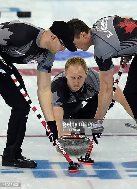 Canada's Brad Jacobs throws the stone as teammates EJ Harnden and Ryan Harnden brush the ice surface during the Men's Curling Gold Medal Game between...