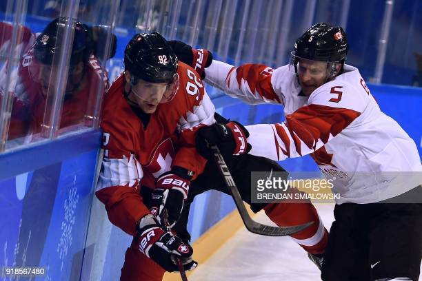 Canada's Chay Genoway checks Switzerland's Gaetan Haas in the men's preliminary round ice hockey match between Switzerland and Canada during the...