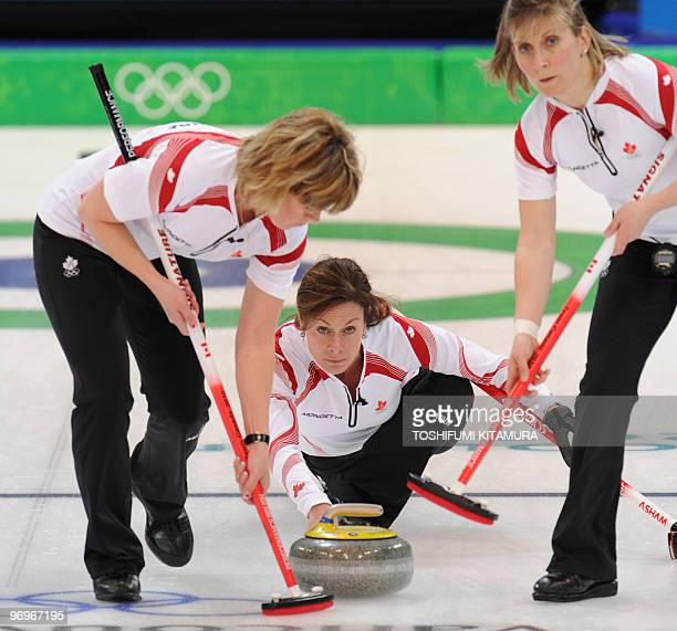 Canada's Cheryl Bernard watches the stone while her teammates Susan O'Connor and Cori Bartel sweep the ice during their Vancouver Winter Olympics...