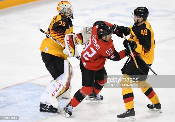 TOPSHOT Canada's Christian Thomas fights with Germany's Frank Hordler in the men's semifinal ice hockey match between Canada and Germany during the...