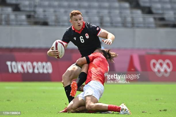Canada's Connor Braid is tackled by Britain's Dan Bibby in the men's pool B rugby sevens match between Britain and Canada during the Tokyo 2020...