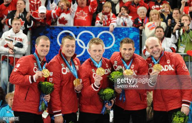Canada's curling team Canada's Kevin Martin John Morris Marc Kennedy Ben Hebert and Adam Enright display their gold medal on the podium during the...