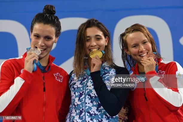 Canada's Danica Ludlow Argentina's Delfina Pignatiello and Canada's Alyson Ackman pose on the podium after receiving their silver gold amd bronze...