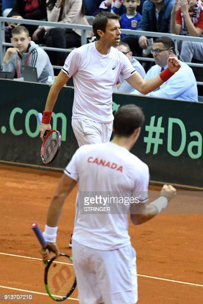 Canada's Daniel Nestor flanked by Vasek Pospis celebrate after scoring a point against Croatia's Marin Cilic and Ivan Dodig during the Davis Cup...