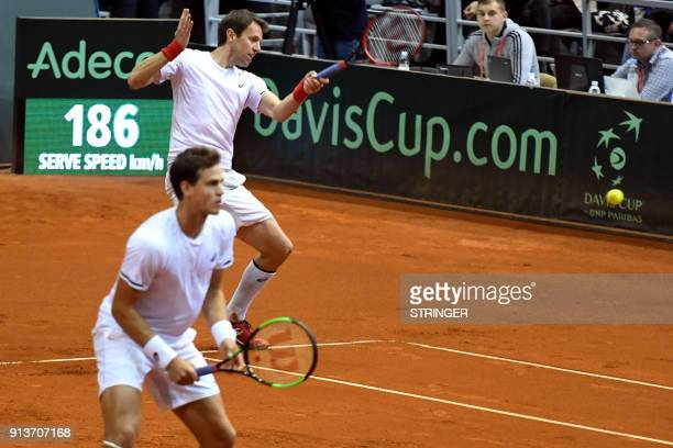Canada's Daniel Nestor flanked by Vasek Pospis hits a return against Croatia's Marin Cilic and Ivan Dodig during the Davis Cup World Group fiorst...