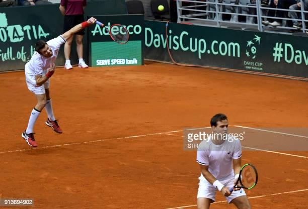 Canada's Daniel Nestorserves as partner Vasek Pospis looks towards opponents Croatia's Marin Cilic and Ivan Dodig during the first round Davis Cup...
