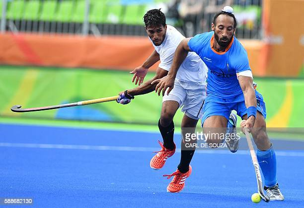 Canada's David Carter and India's Sardar Singh vie during the mens's field hockey India vs Canada match of the Rio 2016 Olympics Games at the Olympic...