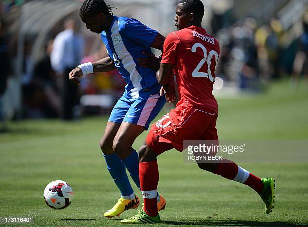 Canada's Donell Henry vies with Martinique's Frederic Piquionne during the 2013 CONCACAF Gold Cup opener on July 7 2013 at the Rose Bowl in Pasadena...