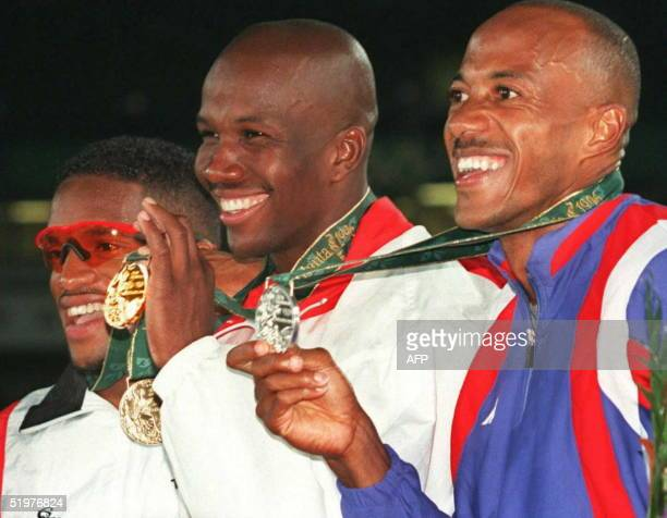 Canada's Donovan Bailey smiles as he displays his gold medal during the medals ceremony after winning the men's Olympic100m race 27 July with a world...
