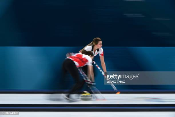 Canada's Emma Miskew and Lisa Weagle brush in front of the stone during the curling women's round robin session between the US and Canada during the...