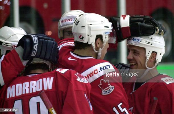 Canada's Eric Brewer is congratulated by team mates Dany Heatley and Brendan Morrow after scoring 41 during a first round group D match against...