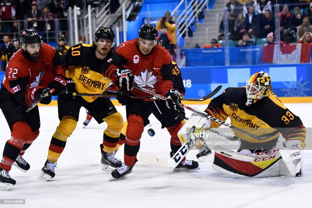 TOPSHOT - Canada's Eric O'Dell (L) and Canada's Rene Bourque (2nd R) fight for the puck with Germany's Christian Ehrhoff (2nd L) in the men's semi-final ice hockey match between Canada and Germany during the Pyeongchang 2018 Winter Olympic Games at the Gangneung Hockey Centre in Gangneung on February 23, 2018. / AFP PHOTO / Brendan Smialowski