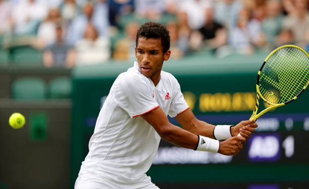 Canada's Felix Auger-Aliassime returns against Australia's Nick Kyrgios during their men's singles third round match on the sixth day of the 2021...