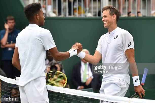 Canada's Felix AugerAliassime shakes hands with Canada's Vasek Pospisil after AugerAliassime won their men's singles first round match on the first...