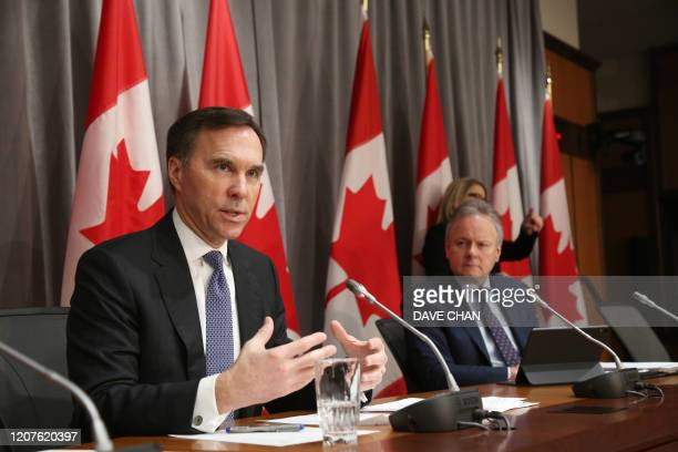 Canada's Finance Minister Bill Morneau speaks during a news conference March 18 2020 in Ottawa Ontario as Bank of Canada Governor Stephen Poloz looks...