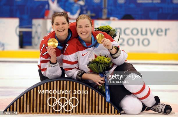 Canada's forward Jennifer Botterill and forward Cherie Piper show off their gold medals during the medals ceremony following their win over the USA...