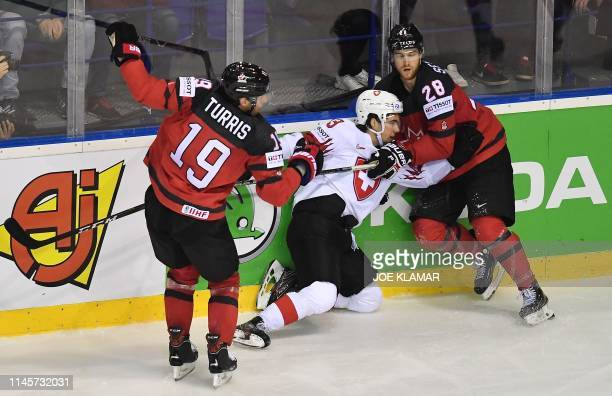 Canada's forward Kyle Turris and Canada's defender Damon Severson vie for the puck with Switzerland's forward Nico Hischier during the IIHF Men's Ice...