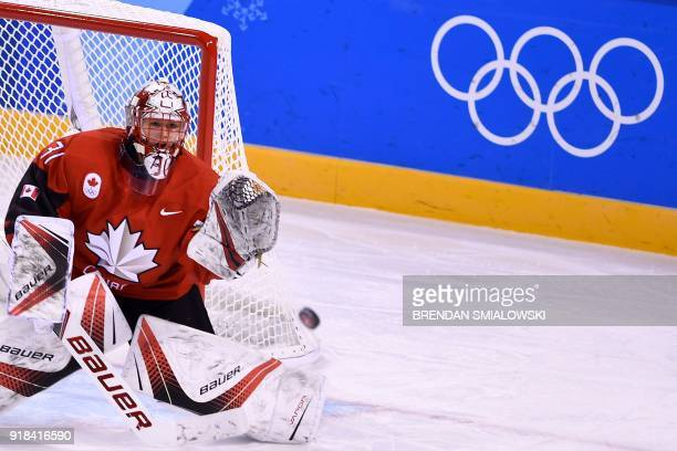Canada's Genevieve Lacasse attempts to make a save in the women's preliminary round ice hockey match between the US and Canada during the Pyeongchang...