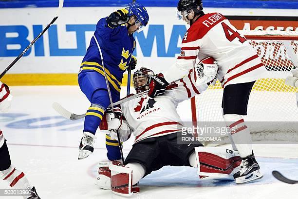 Canada's goalie Mackenzie Blackwood gets pinned between Sweden's Axel Holmstrom and Canada's Haydn Fleury during the 2016 IIHF World Junior U20 Ice...