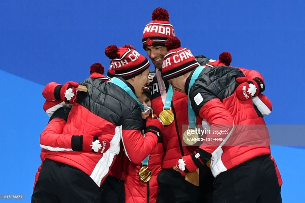 Canada's gold medal-winning team celebrate on the podium during the medal ceremony for the figure skating team event at the Pyeongchang Medals Plaza during the Pyeongchang 2018 Winter Olympic Games in Pyeongchang on February 12, 2018. / AFP PHOTO / Fabrice COFFRINI