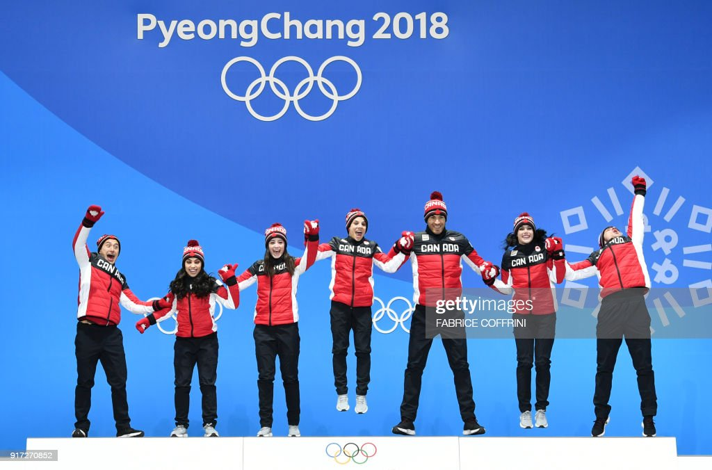 Canada's gold medal-winning team jump on the podium during the medal ceremony for the figure skating team event at the Pyeongchang Medals Plaza during the Pyeongchang 2018 Winter Olympic Games in Pyeongchang on February 12, 2018. / AFP PHOTO / Fabrice COFFRINI