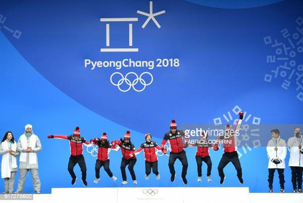 Canada's gold medalwinning team jump on the podium during the medal ceremony for the figure skating team event at the Pyeongchang Medals Plaza during...