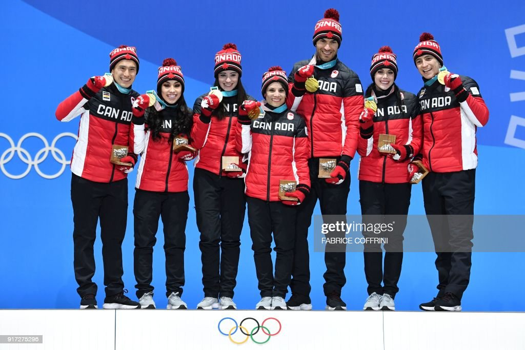 Canada's gold medal-winning team pose on the podium during the medal ceremony for the figure skating team event at the Pyeongchang Medals Plaza during the Pyeongchang 2018 Winter Olympic Games in Pyeongchang on February 12, 2018. / AFP PHOTO / Fabrice COFFRINI