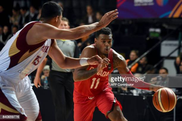 TOPSHOT Canada's guard Xavier RathanMayes drives the ball marked by Venezuela's center Windi Graterol during their 2017 FIBA Americas Championship...
