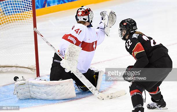 Canada's Hayley Wickenheiser scores past Switzerland's goalkeeper Florence Schelling during the Women's Ice Hockey Group A match Canada vs...