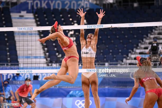 Canada's Heather Bansley attempts a shot past Latvia's Tina Graudina in their women's beach volleyball quarter-final match between Latvia and Canada...