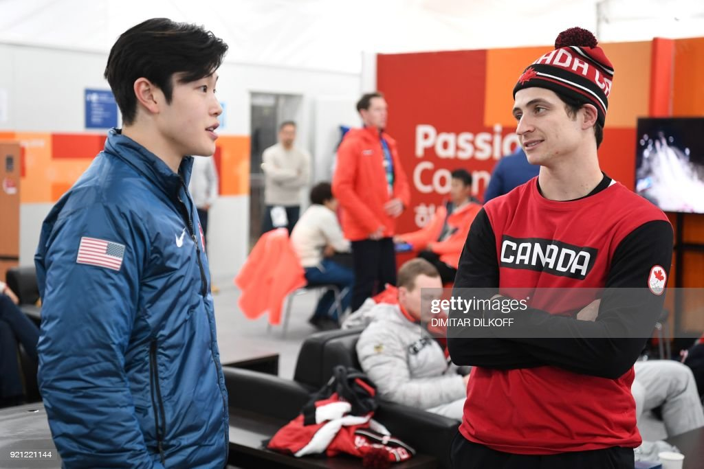 Canada's ice dance gold medallist Scott Moir (R) chats with USA's bronze medallist Alex Shibutani backstage at the Athletes' Lounge during the medal ceremonies at the Pyeongchang Medals Plaza during the Pyeongchang 2018 Winter Olympic Games in Pyeongchang on February 20, 2018. / AFP PHOTO / Dimitar DILKOFF