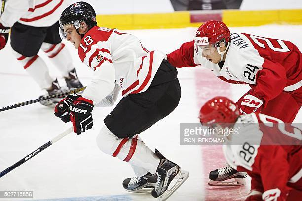 Canada's Jake Virtanen and Denmark's Niklas Andersen chase the puck during the 2016 IIHF World Junior Ice Hockey Championship match between Canada...