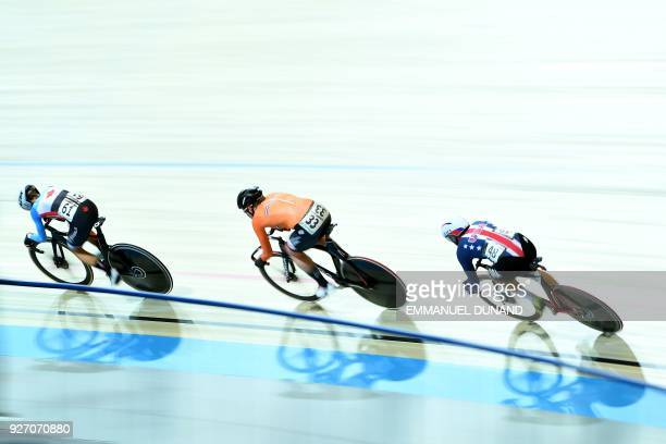 Canada's Jasmin Duehring Netherlands Kirsten Wild and US cyclist Jennifer Valente compete in the women's points race final during the UCI Track...