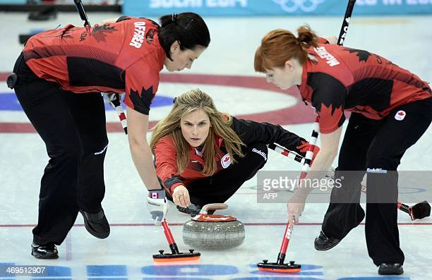Canada's Jennifer Jones trows the stone as her team mates Jill Officer and Dawn McEwen sweep during the Women's Curling Round Robin Session 9 against...