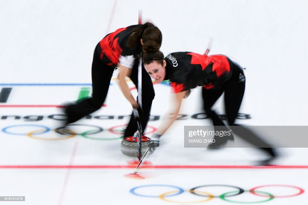TOPSHOT - Canada's Joanne Courtney (R) brushes in front of the stone during the curling women's round robin session between Canada and Switzerland during the Pyeongchang 2018 Winter Olympic Games at the Gangneung Curling Centre in Gangneung on February 18, 2018. / AFP PHOTO / WANG Zhao