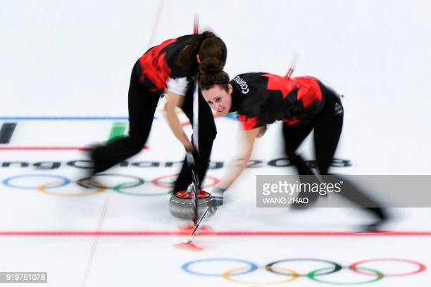 Canada's Joanne Courtney brushes in front of the stone during the curling women's round robin session between Canada and Switzerland during the...