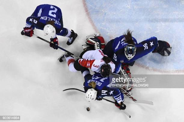 Canada's Jocelyne Larocque fights for the puck with US players in the women's gold medal ice hockey match between the US and Canada during the...