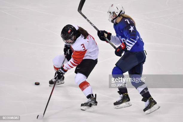 Canada's Jocelyne Larocque fights for the puck with USA's Monique LamoureuxMorando in the women's gold medal ice hockey match between the US and...