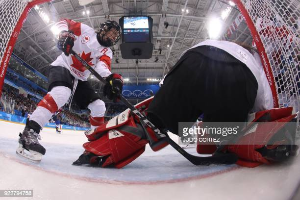 Canada's Jocelyne Larocque reaches around teammate Shannon Szabados in the women's gold medal ice hockey match between the US and Canada during the...