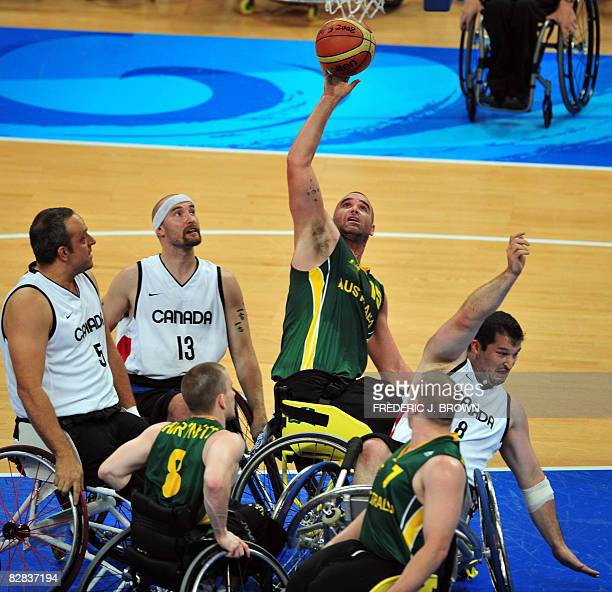 Canada's Joey Johnson takes a fall while Australia's Brad Ness wins the rebound as Canada's Yvon Rouillard and Chris Stoutenberg look on in their...