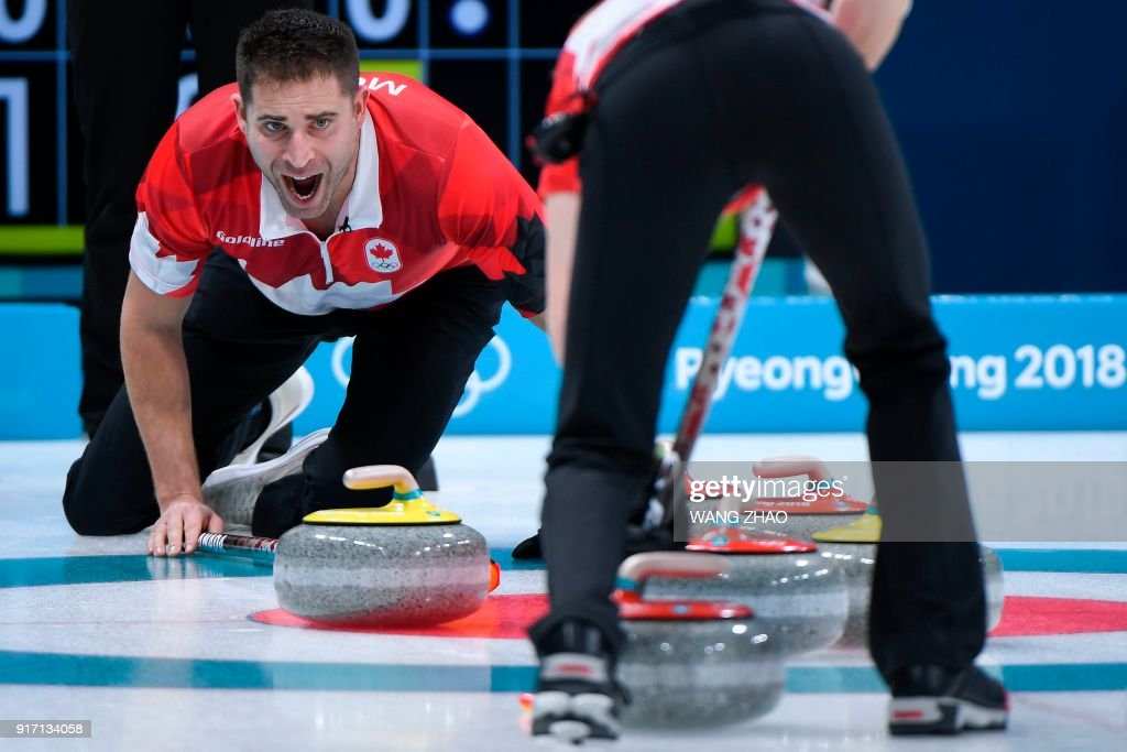 Canada's John Morris shouts instructions as Kaitlyn Lawes brushes the ice surface during the Pyeongchang 2018 Winter Olympic Games at the Gangneung Curling Centre in Gangneung on February 12, 2018. / AFP PHOTO / WANG Zhao