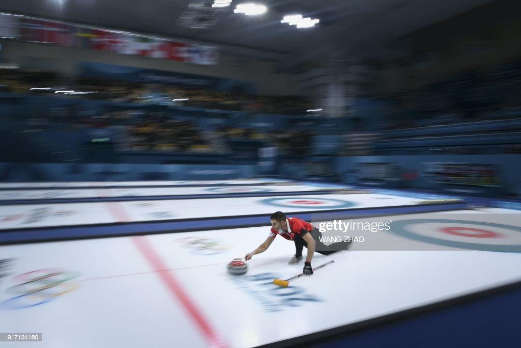 Canada's John Morris throws the stone during the Pyeongchang 2018 Winter Olympic Games at the Gangneung Curling Centre in Gangneung on February 12, 2018. / AFP PHOTO / WANG Zhao