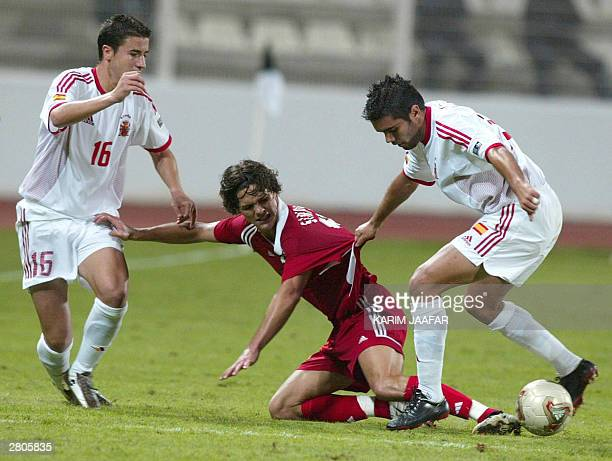 Canada's Josh Simpson fights for the ball with Gabi and Bouzon of Spain's during their FIFA World Youth Championship match in Abu Dhabi 12 December...