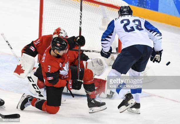 Canada's Karl Stollery adn Finland's Joonas Kemppainen look on as the puck goes past the net in the men's quarterfinal ice hockey match between...