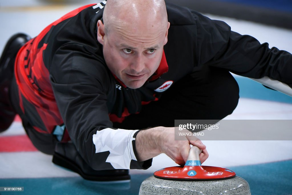 Canada's Kevin Koe throws the stone during the curling men's round robin session between Canada and Britain during the Pyeongchang 2018 Winter Olympic Games at the Gangneung Curling Centre in Gangneung on February 14, 2018. / AFP PHOTO / WANG Zhao