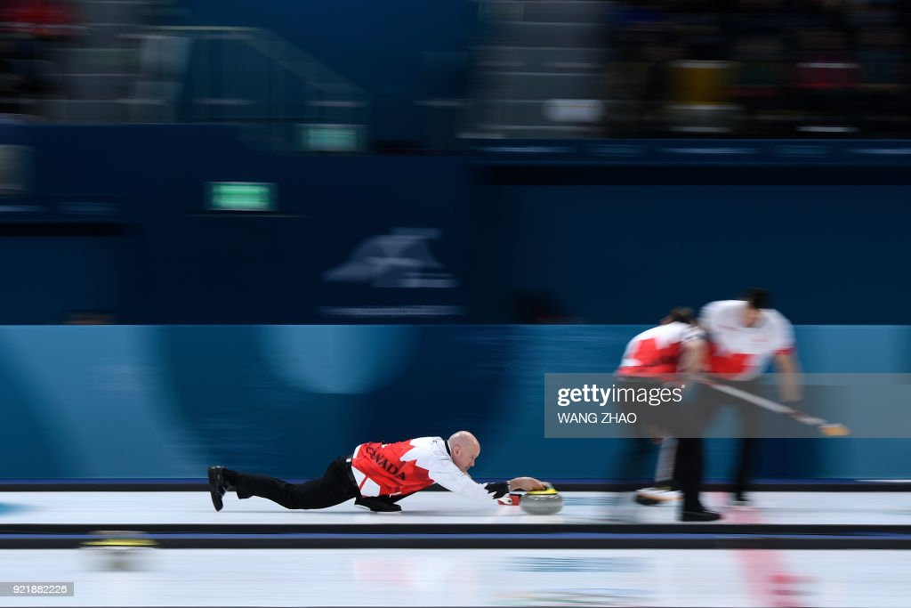 TOPSHOT - Canada's Kevin Koe throws the stone during the curling men's round robin session between Denmark and Canada during the Pyeongchang 2018 Winter Olympic Games at the Gangneung Curling Centre in Gangneung on February 21, 2018. / AFP PHOTO / WANG Zhao