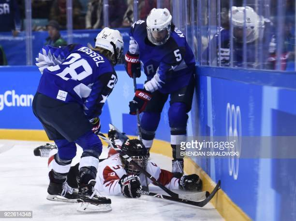 Canada's Lauriane Rougeau falls as USA's Amanda Kessel and USA's Megan Keller look on in the women's gold medal ice hockey match between Canada and...