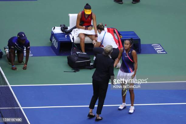 Canada's Leylah Fernandez speaks to an official as Britain's Emma Raducanu has her knee bandaged during their 2021 US Open Tennis tournament women's...