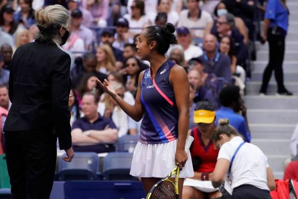 Canada's Leylah Fernandez speaks to an official as Britain's Emma Raducanu receives medical attention for a cut on her knee during her 2021 US Open...