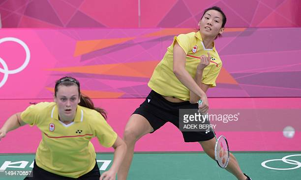 Canada's Li Michele smashes a shuttle cock next to teammate Alex Bruce during the women's doubles batminton match against South Korea's Kim Ha Na and...